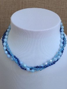 Gargantilha em três voltas com miçangas peroladas azul claro, miçangas transparente azul escuro, mini pérola azul, mini miçangas azul claro e azul escuro - fecho tipo rosca prateado.