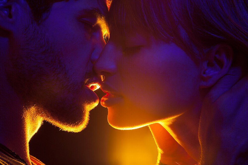 casal se beijando com luz roxa