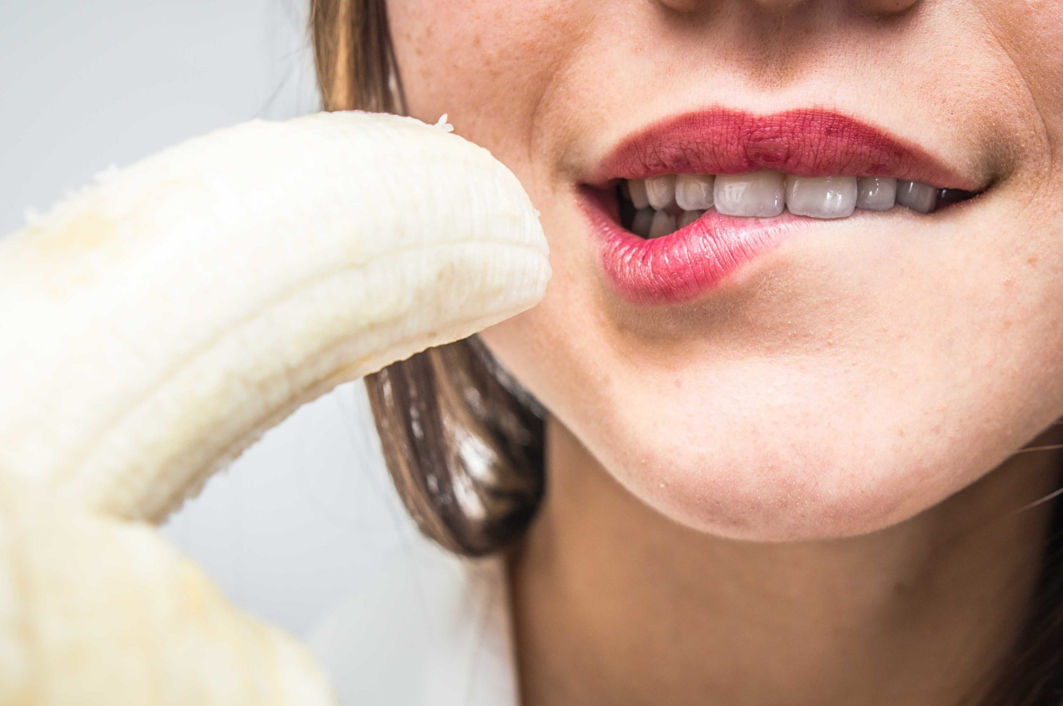 banana do lado da boca de uma mulher