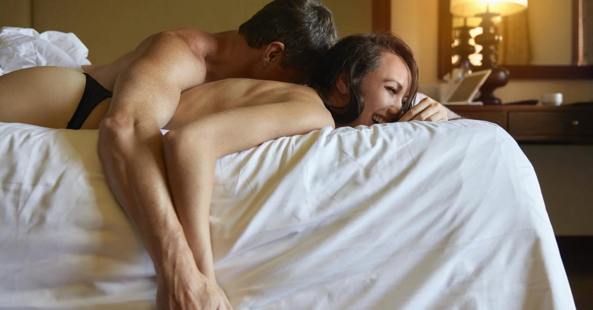 casal feliz deitado na cama