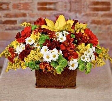 Cesta de flores nobres e do campo em tons de amarelo e laranja.
