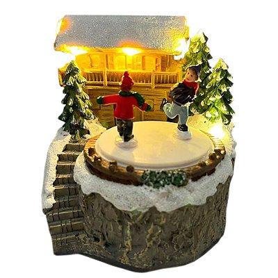 Brinquedo de natal casinha com árvores e patinadores