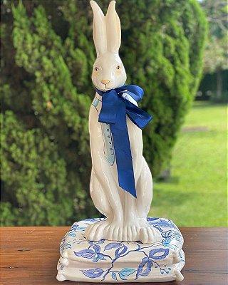 Coelho de cerâmica com almofada azul