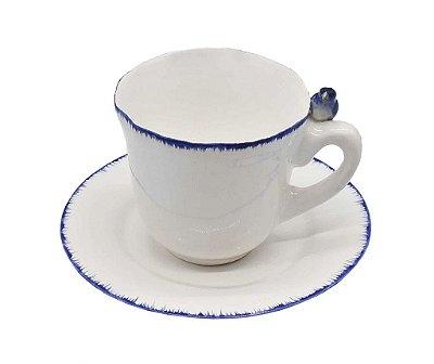 Xícara de chá branca com borda pincelada azul com passarinho