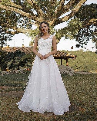 Vestido de noiva longo com bordado em pedrarias e renda, leve e fluido.