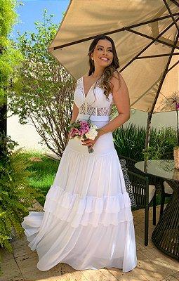 Vestido de noiva branco, corpo estruturado em renda, e saia com camadas em musseline