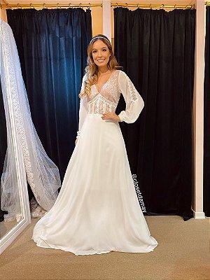 Vestido de noiva longo, em crepe e renda, com mangas longas, e decote V. Para casamento religioso, e civil.