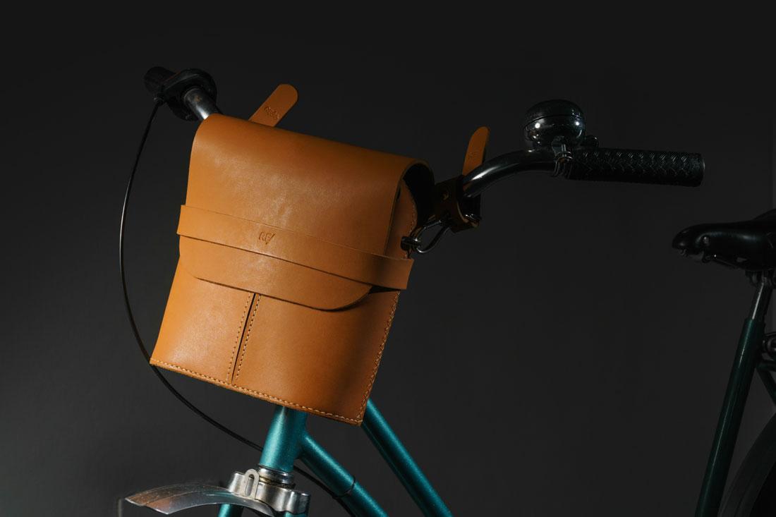 Bolsa Pala em couro caramelo presa ao guidão da bike com os adaptadores de engate rápido