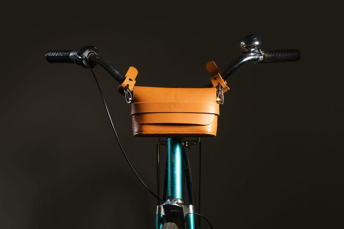 Clutch Pala em couro caramelo presa ao guidão da bicicleta usando os adaptadores