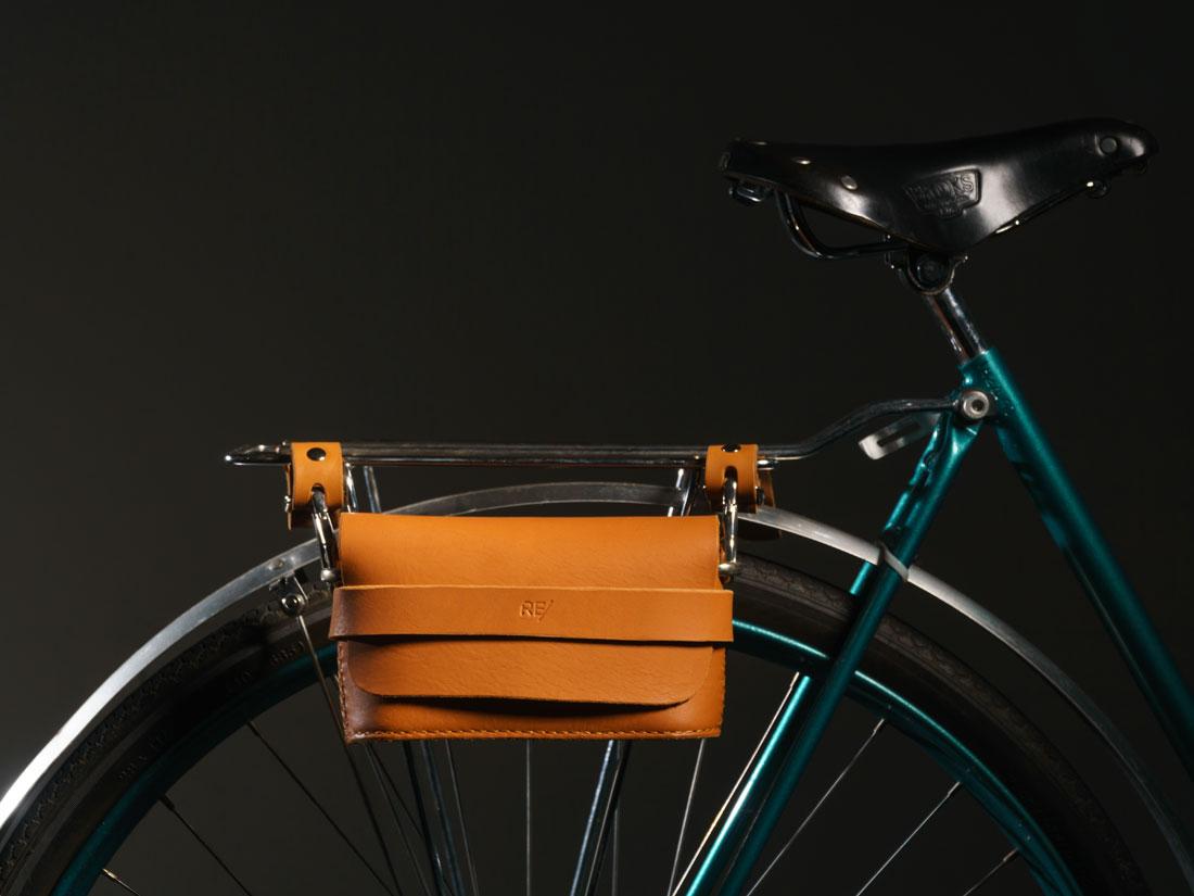 Clutch Pala em couro caramelo presa ao bagageiro da bicicleta usando os adaptadores com engate rápido