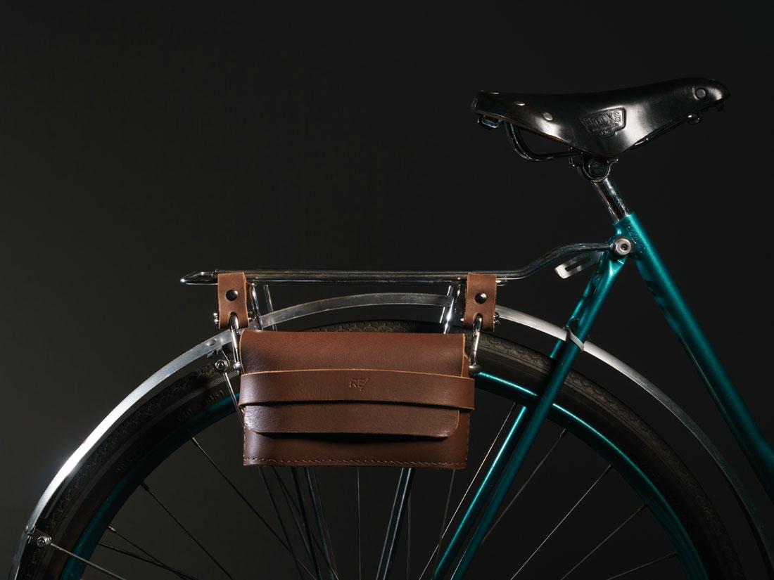 Clutch Pala em couro marrom café presa ao bagageiro da bicicleta usando os adaptadores