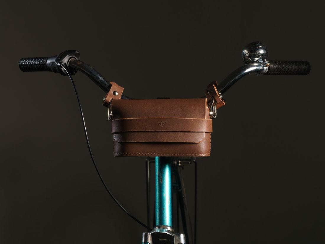 Clutch Pala em couro marrom café presa ao guidão da bicicleta usando os adaptadores com engate rápido