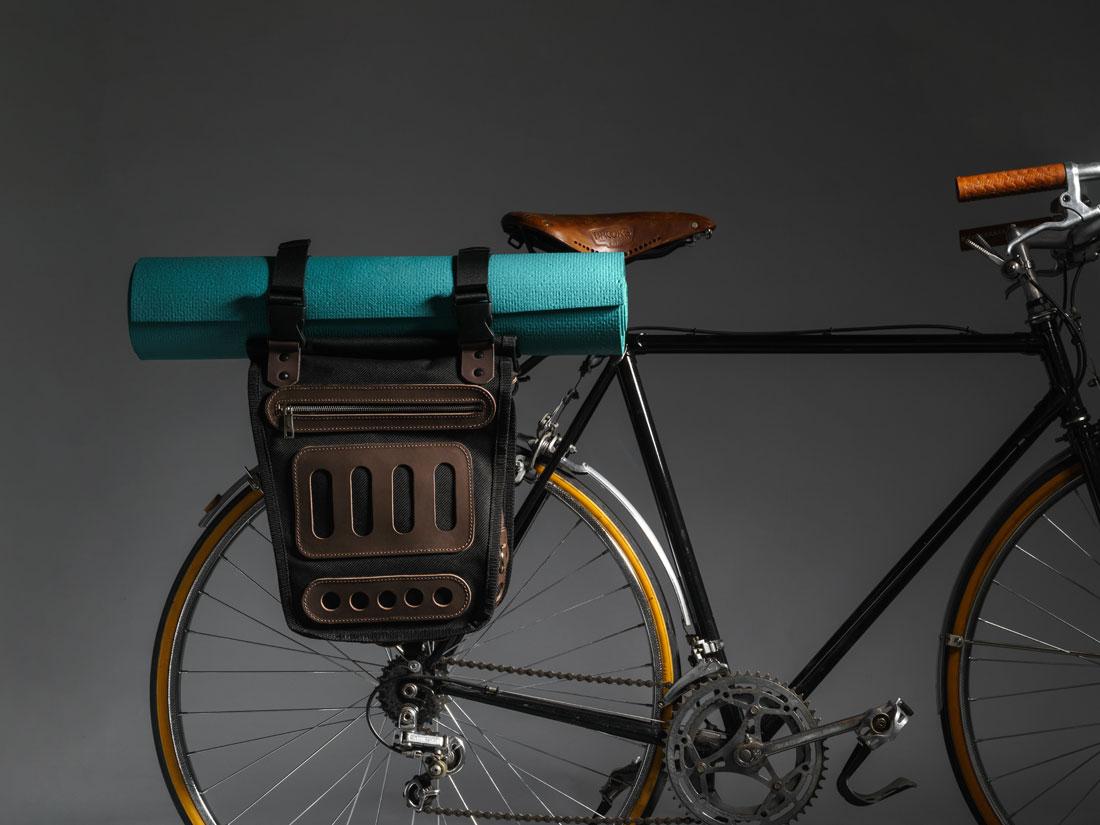 Alforje Montaria no bagageiro da bicicleta levando um tapete de ioga (yoga mat) preso às alças de regulagem da tampa.
