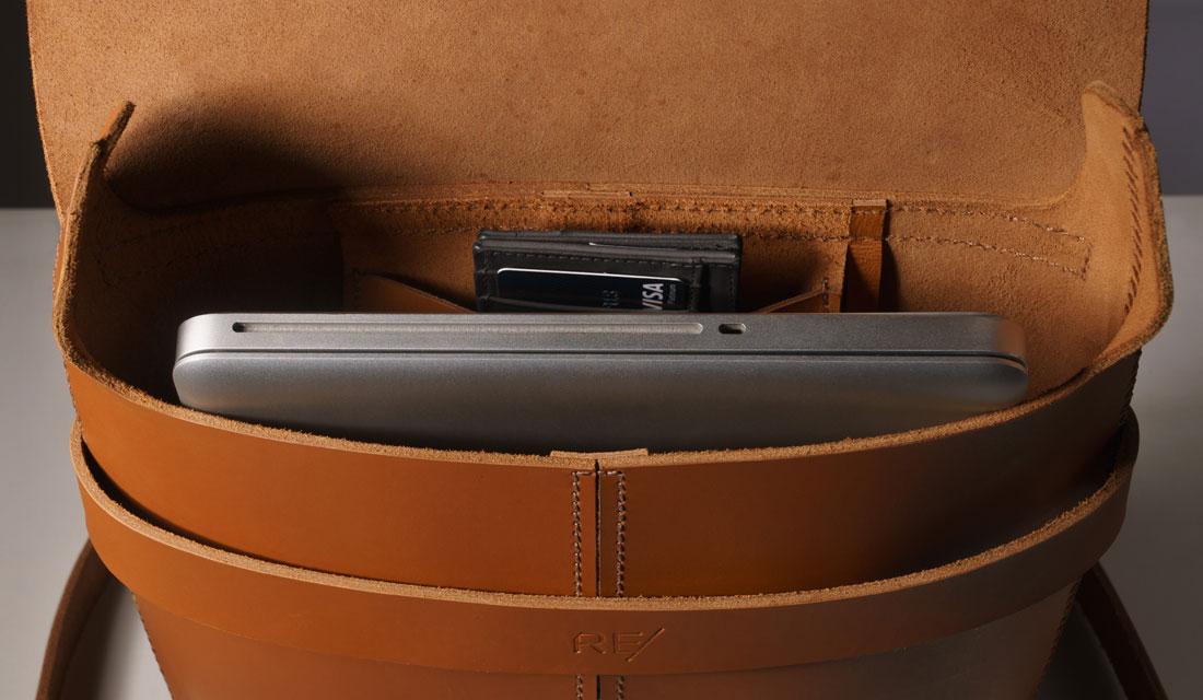 Alforge Pala Caramelo exibindo o bolso interno e um laptop Macbook Pro em seu interior.
