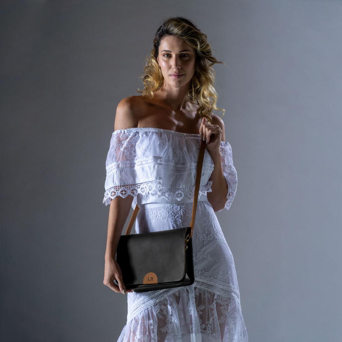 Bolsa de ombro Alma em couro preto com detalhes em caramelo.
