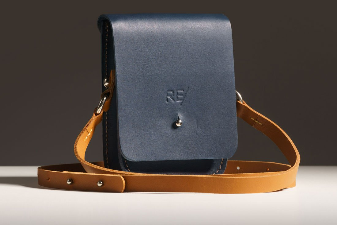 Bolsa Cube azul com alça em couro caramelo.