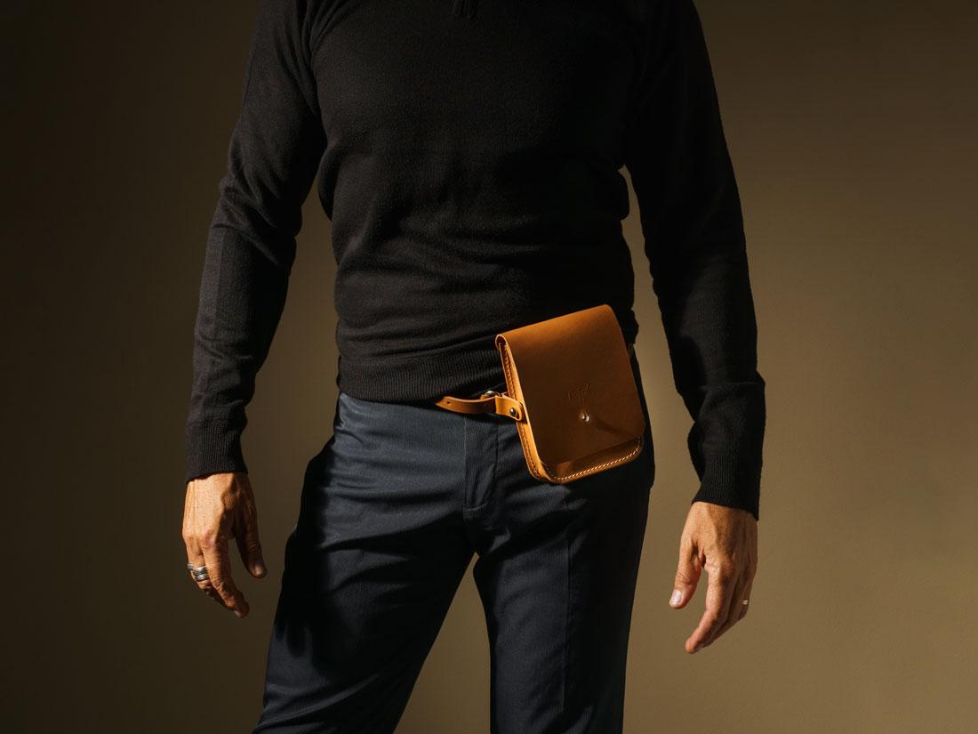 Bolsa Cube em couro caramelo usada na cintura como pochete.