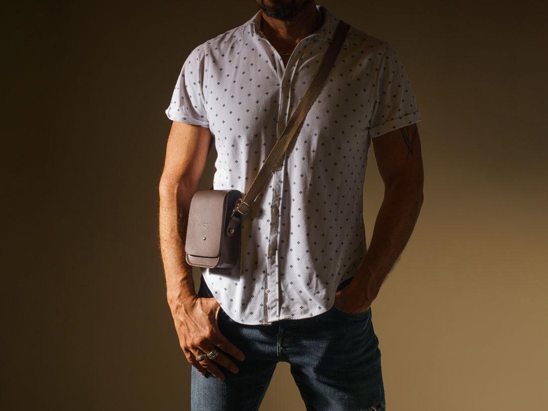 Smartbag Cube em couro marrom café com alça de algodão sendo usada no ombro.