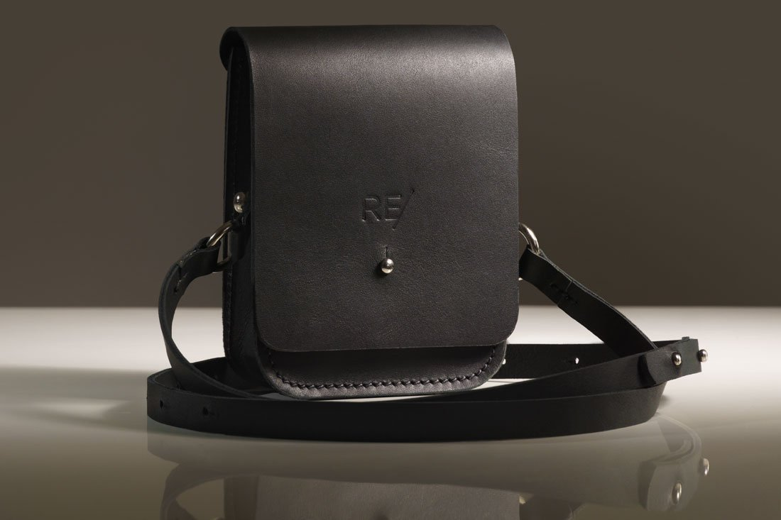 Bolsa Cube preta com alça em couro.