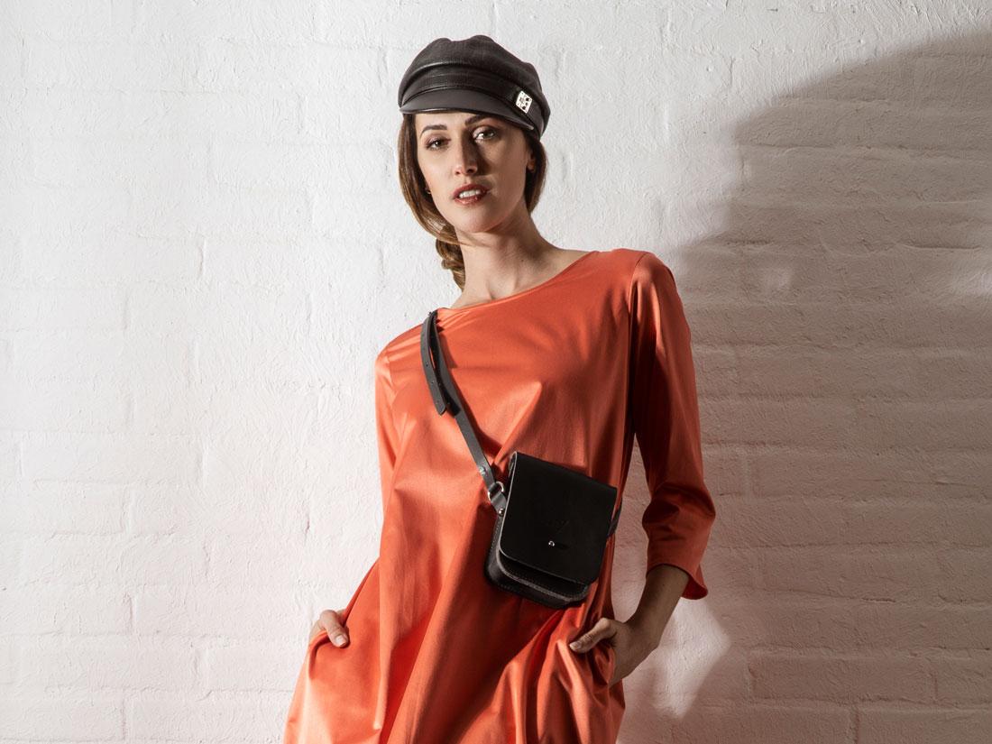 Smartbag Cube em couro preto com alça em couro sendo usada no ombro.