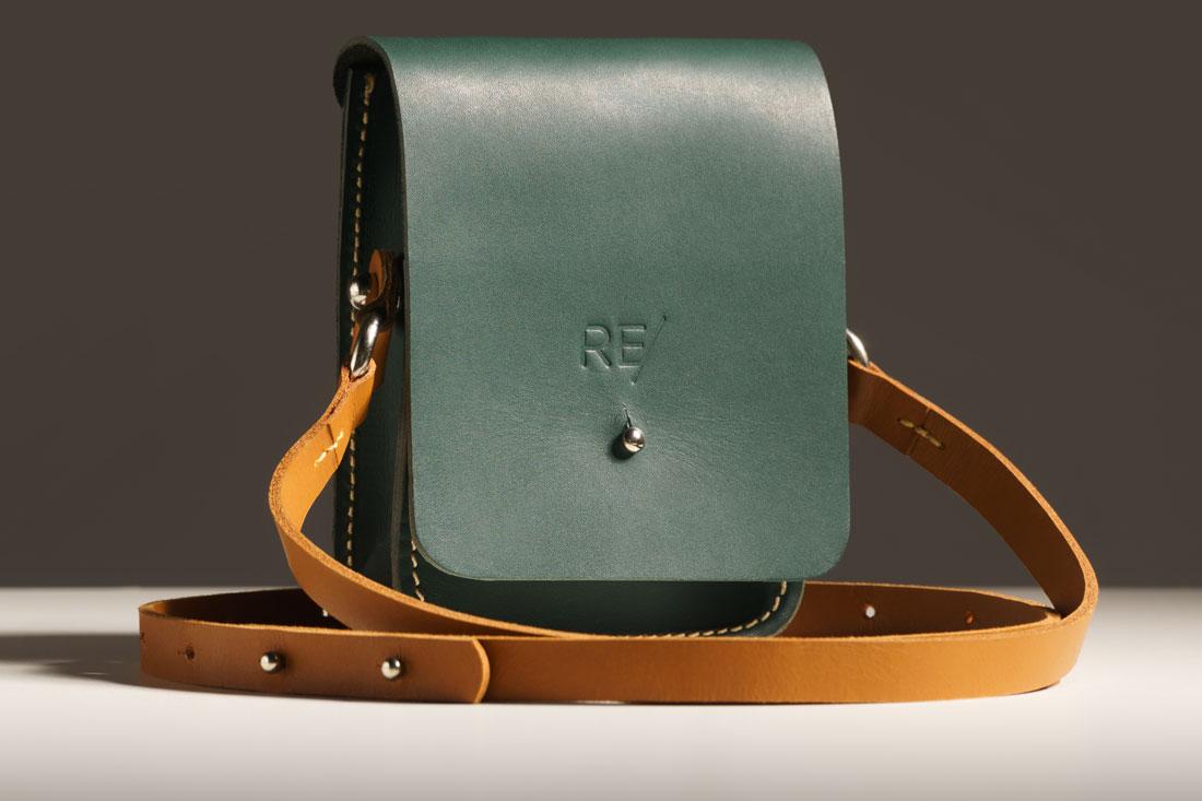 Bolsa Cube verde com alça em couro.