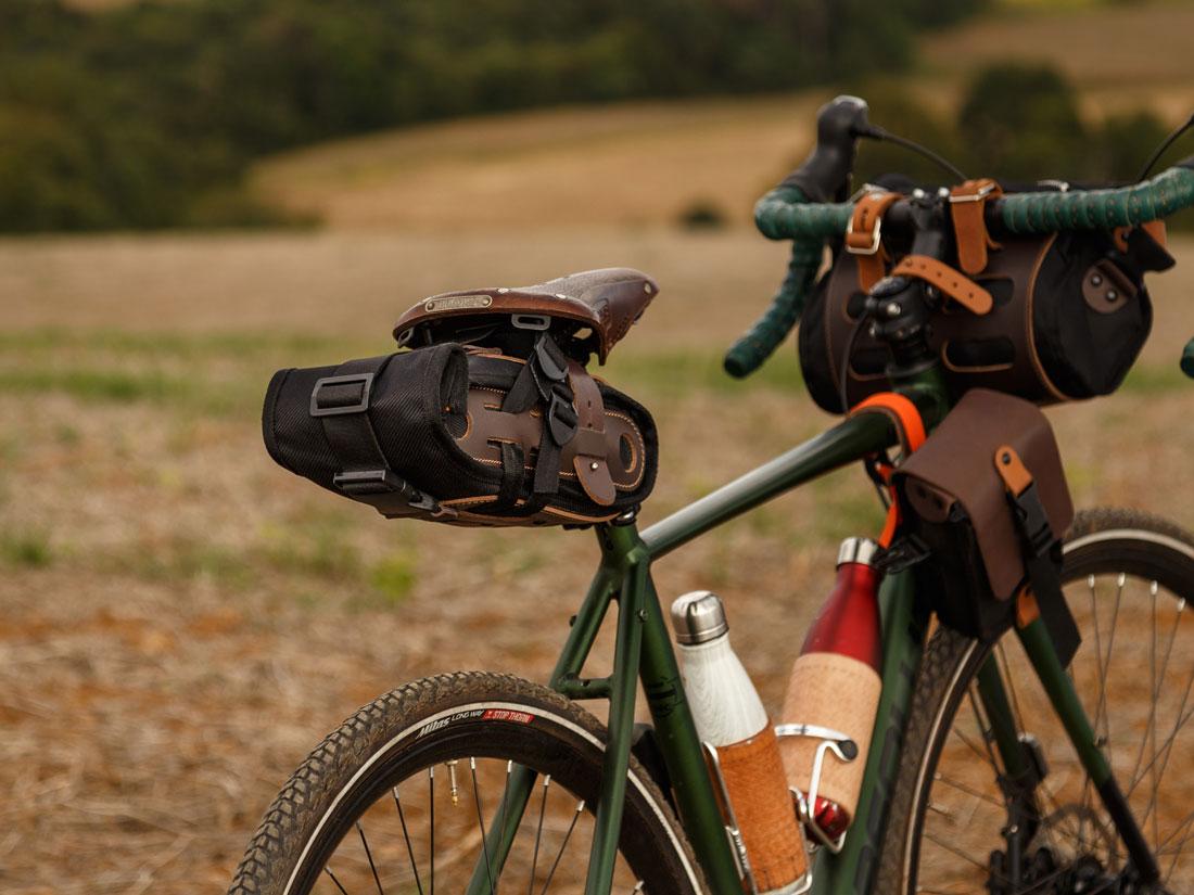 Bolsa de selim Virola presa a um banco Brooks em uma bicicleta gravel, acompanhada de uma bolsa de quadro Galope e da bolsa de guidão Malacara.