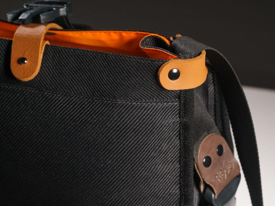 Detalhes da bolsa de guidão Malacara mostrando seu forro em tecido de nylon impermeável e os clips de fechamento em couro que auxiliam no uso da bolsa desenrolada.