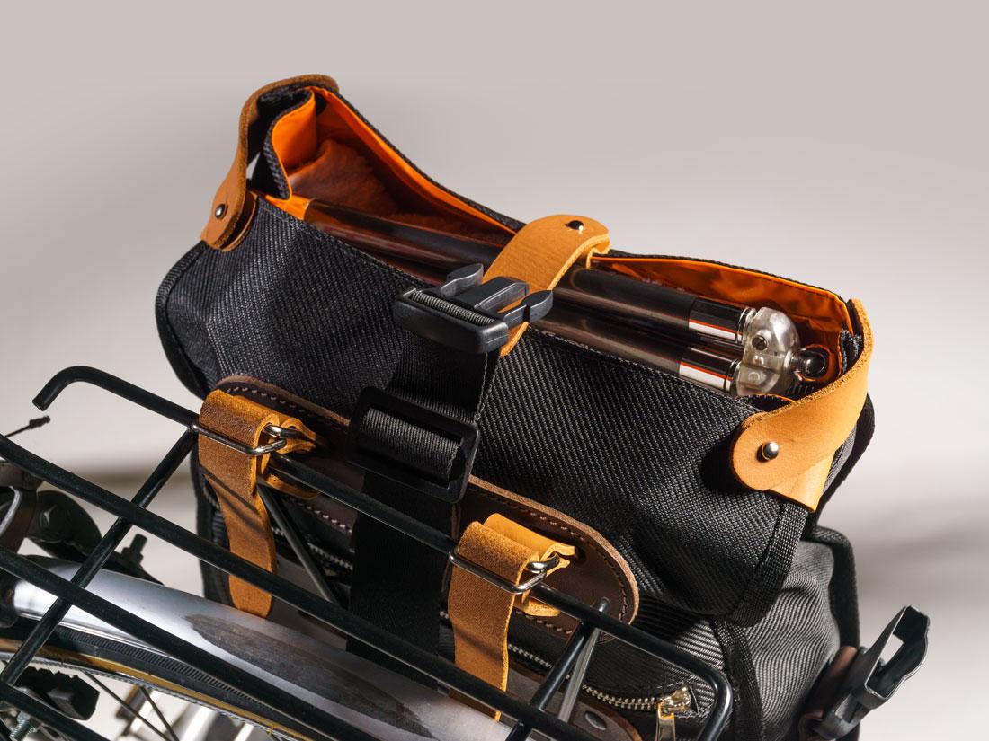 Bolsa Malacara usada como alforge presa ao bagageiro da bicicleta em seu modo aberto.