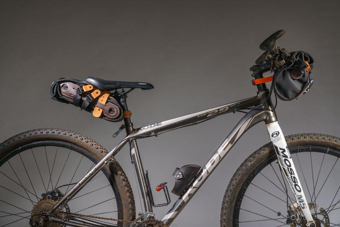 Mountain bike com uma Bolsa Malacara presa ao guidón e uma bolsa de selim Virola presa ao banco.