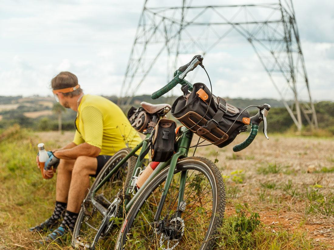 Bike gravel com bolsa Malacara no guidón, bolsa Galope no quadro e bolsa de selim Virola no banco.