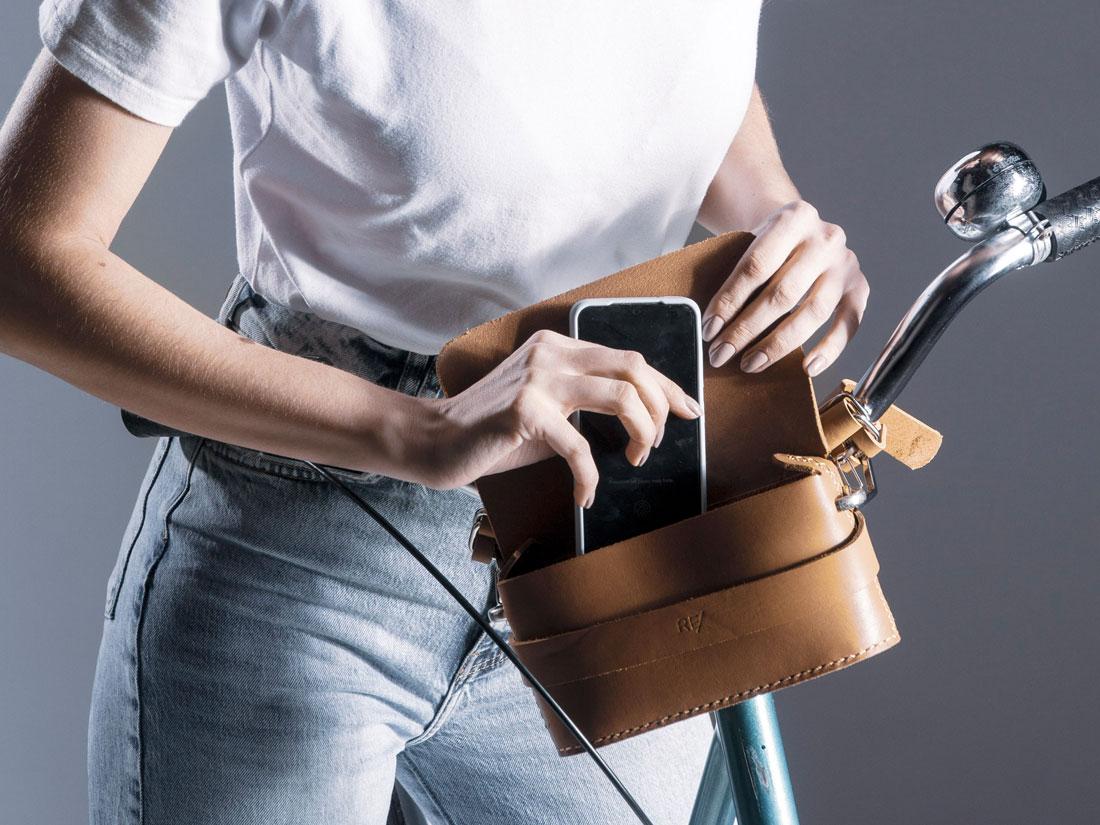 Clutch Pala em couro Caramelo presa ao guidão da bicicleta e usada para guardar um celular.
