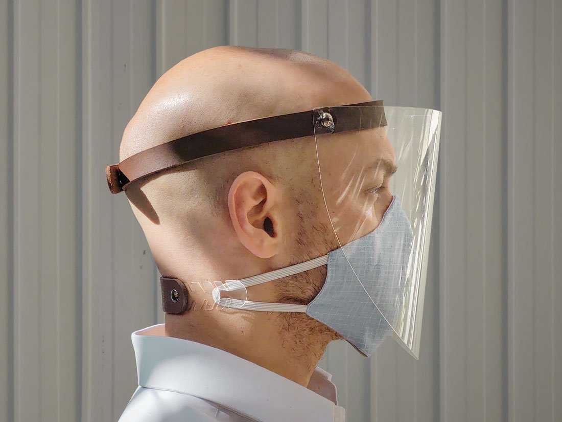 Máscara protetora facial (face shield) em PET com ajuste de cabeça em couro e fechamento em metal + extensor em couro e PET para máscaras bucais de tecido.
