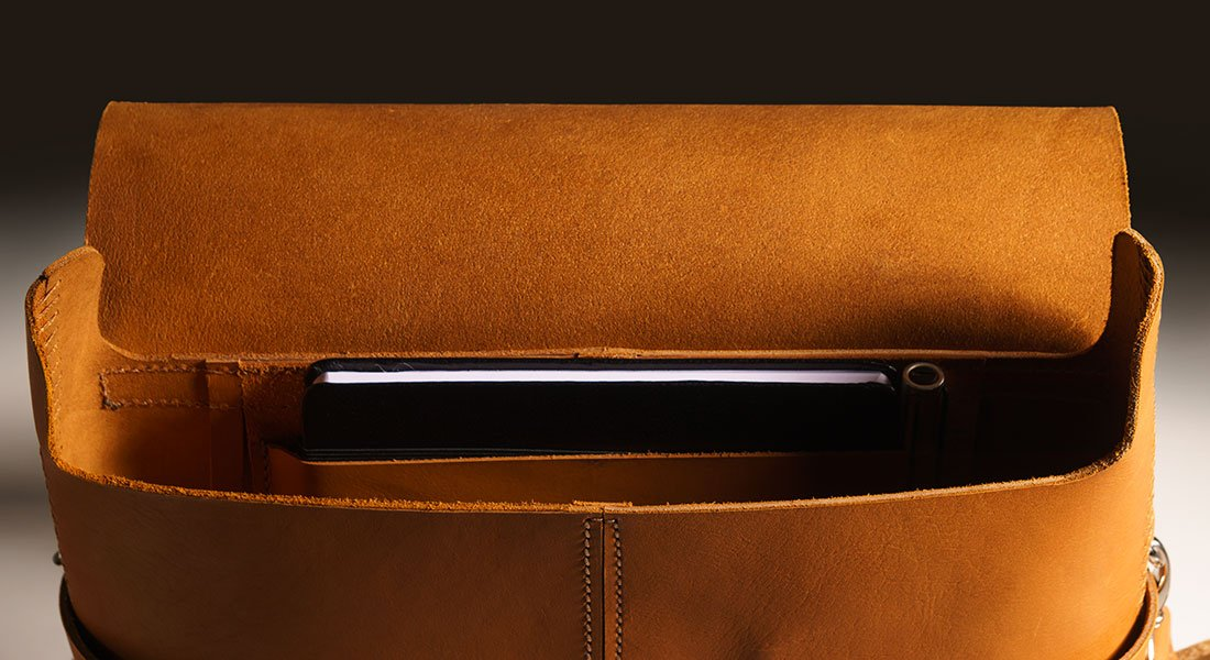 Messenger Pala Grande Caramelo exibindo o seu interior com um caderno de notas no bolso.
