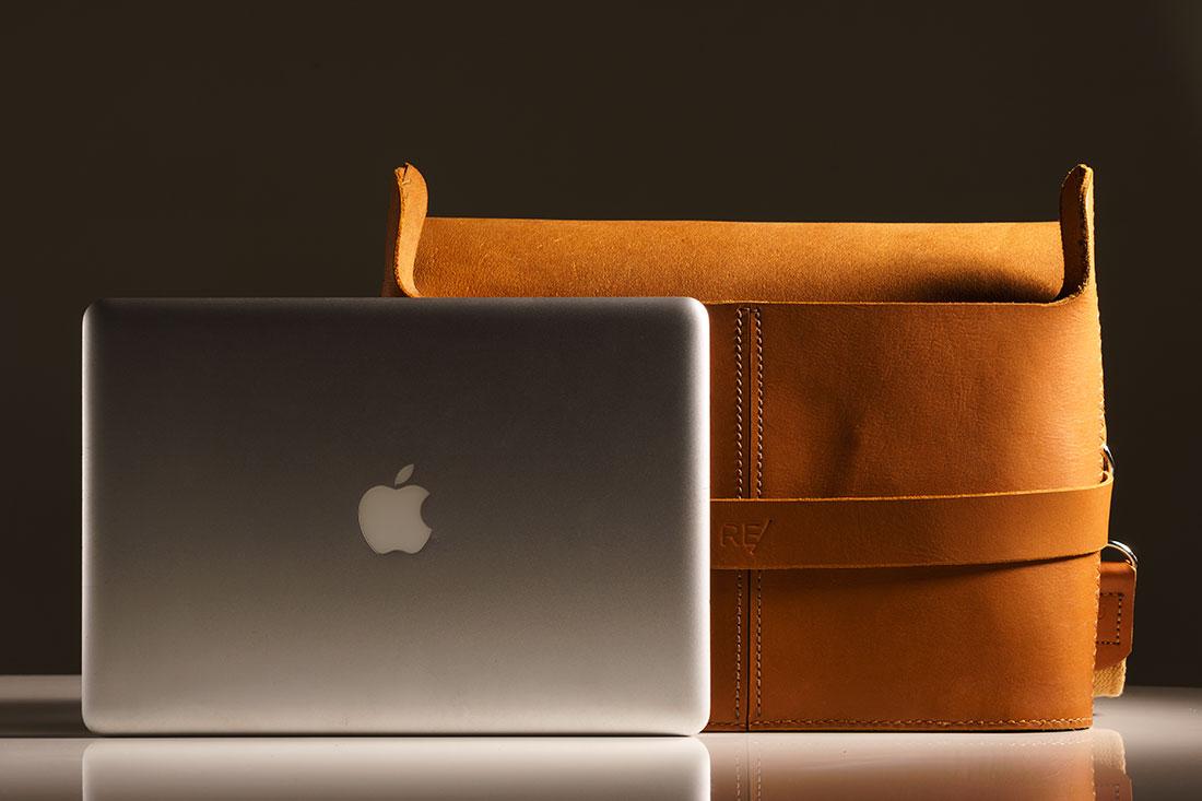 Messenger Pala Grande Caramelo junto de um laptop de 13 polegadas.