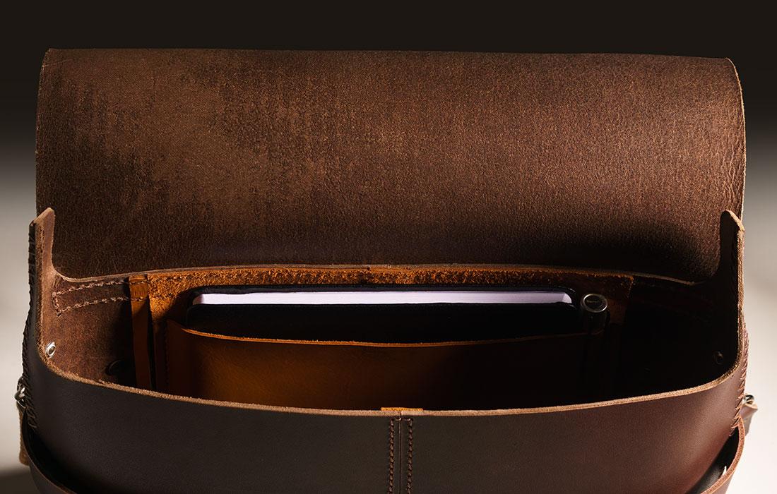 Messenger Pala Grande Marrom Café exibindo o seu interior com um caderno de notas no bolso.