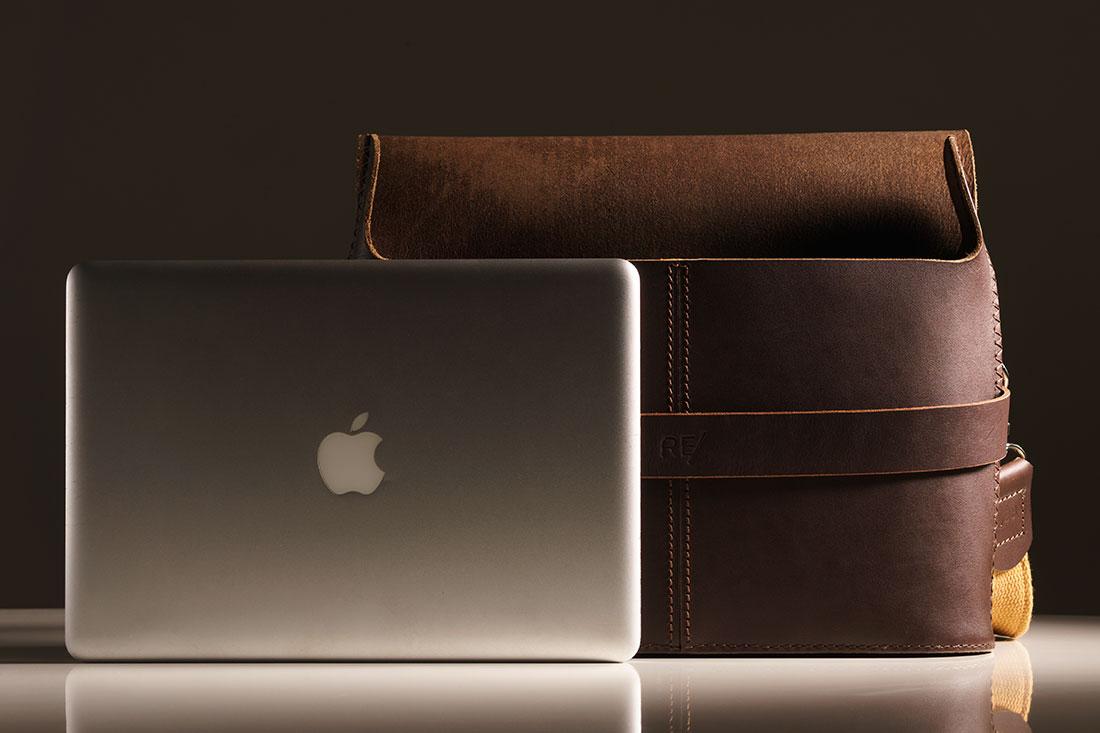 Messenger Pala Grande Marrom Café junto de um laptop de 13 polegadas.