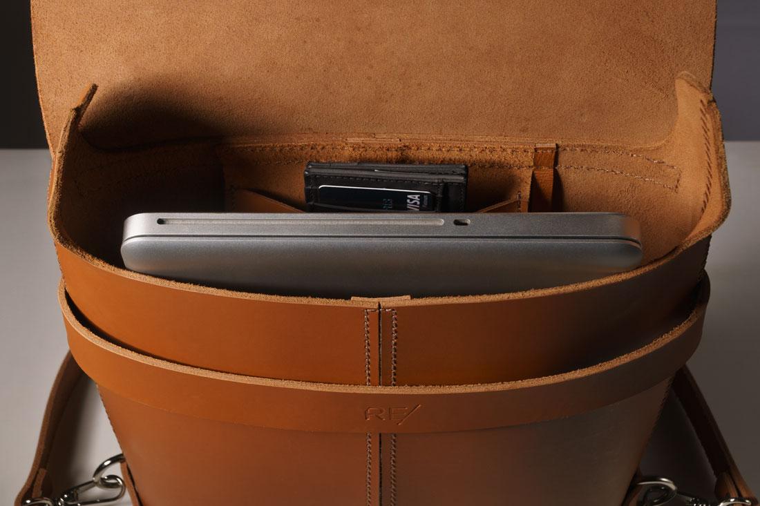 Mochila Pala Caramelo exibindo o bolso interno e um laptop em seu interior.