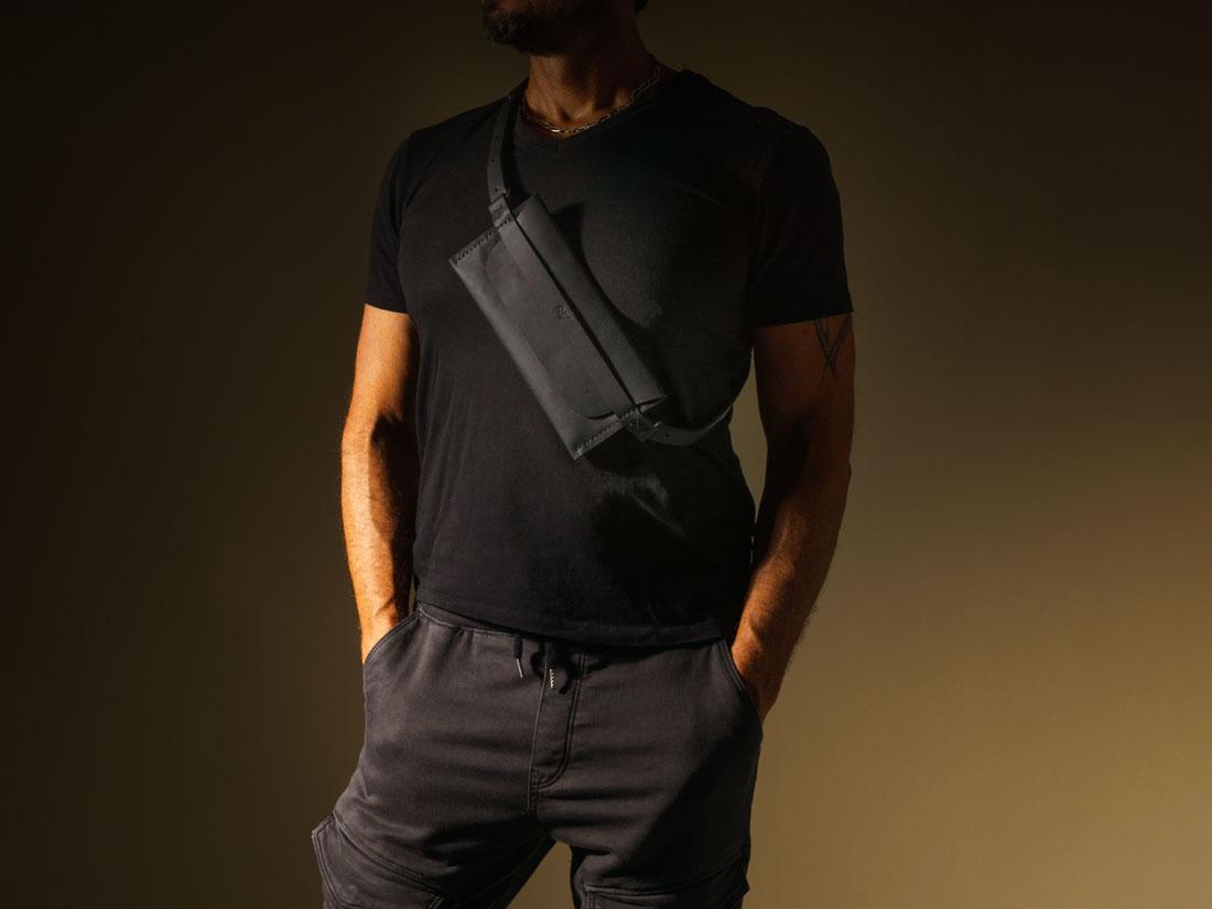 Pochette Pala Slim em couro Preto transpassada no peito como bolsa a tiracolo.