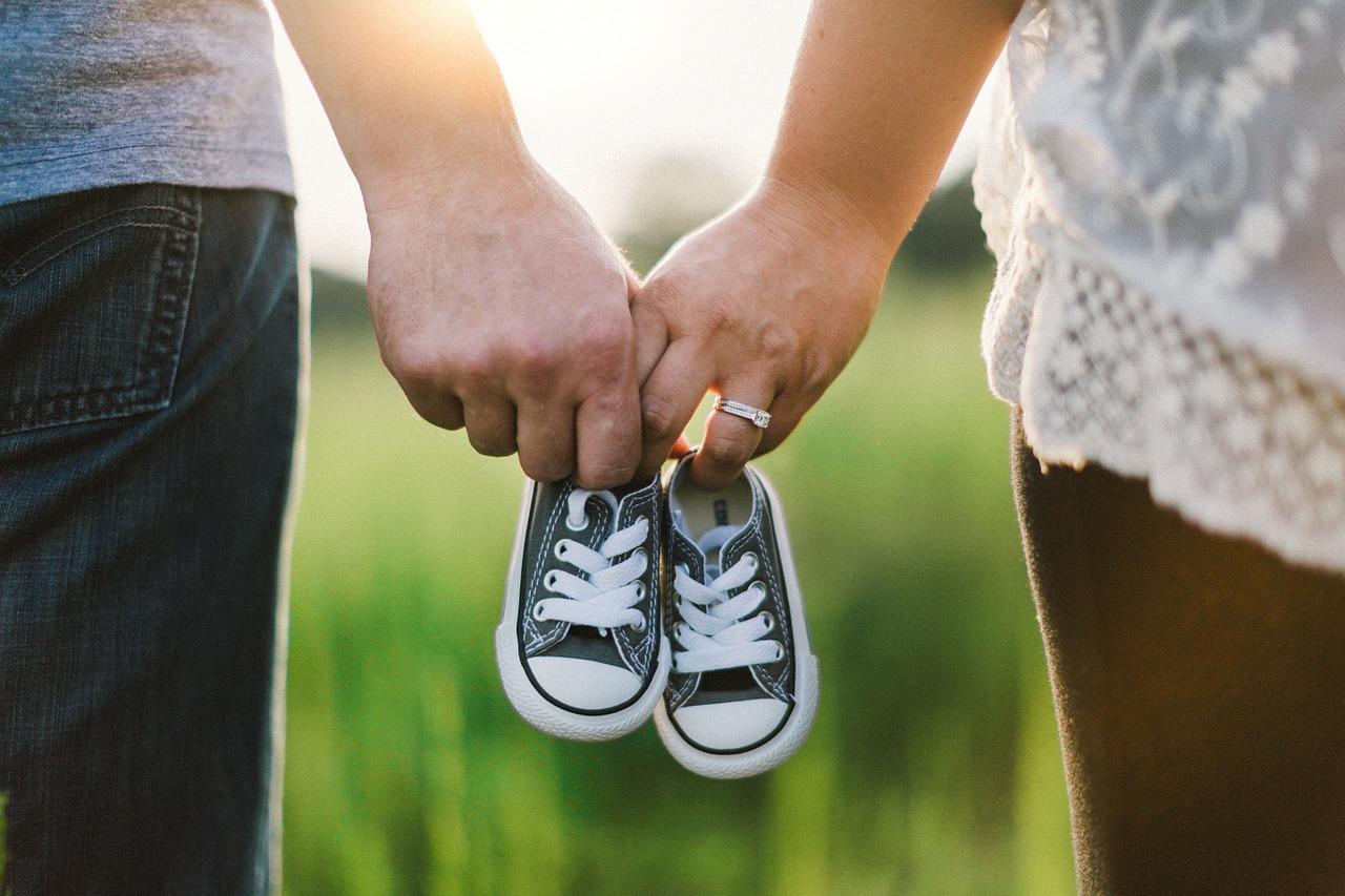 Casal de mãos dadas com aliança segurando um par de sapatinhos para bebê
