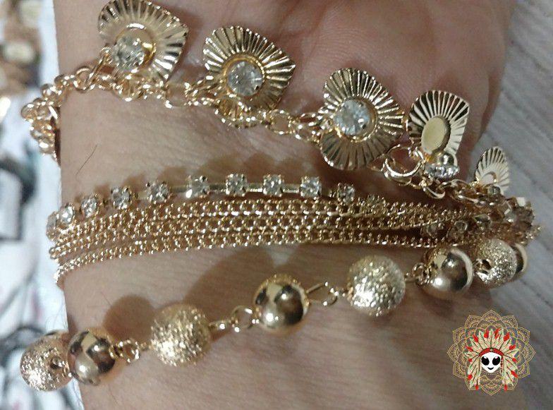 Lindas pulseiras douradas com pedras.