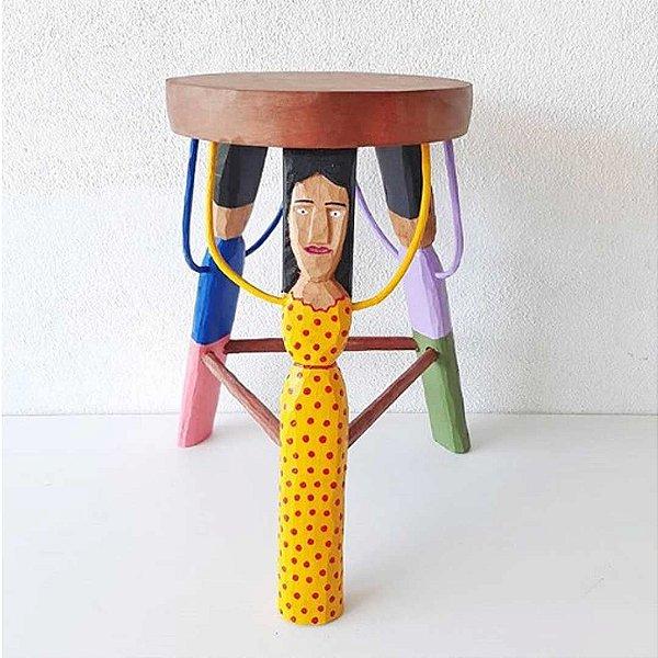 Banquinho de madeira entalhada com três figuras inspiradas no povo brasileiro