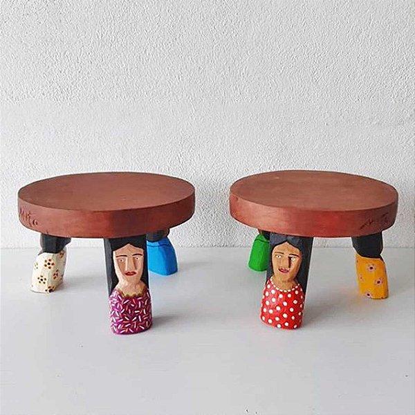 Banquinho de apoio de madeira entalhada com três figuras inspiradas no povo brasileiro