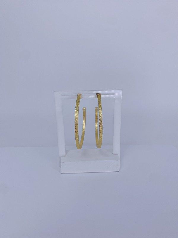 Brinco dourado de argola média fosca com leve brilho