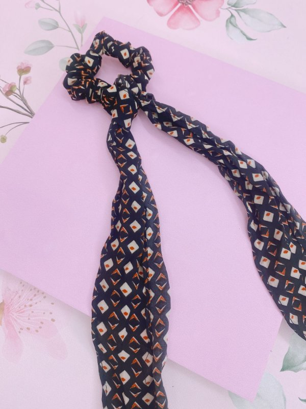 Scrunchie com lenço estampado de preto com quadradinho laranja