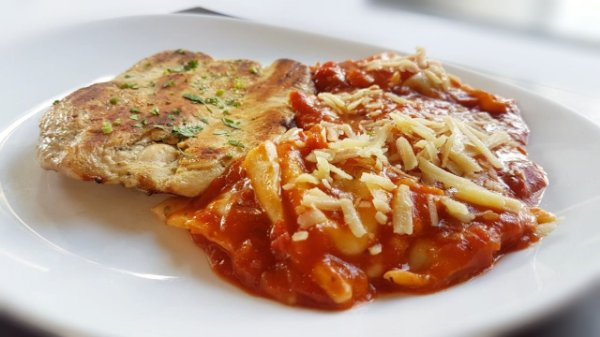 Filé de frango grelhado, servido com ravióli recheado com muçarela ao molho de tomate