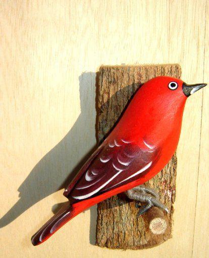 Tiê Sangue - Pássaro esculpido em madeira apoiado em um puleiro de casca de árvore