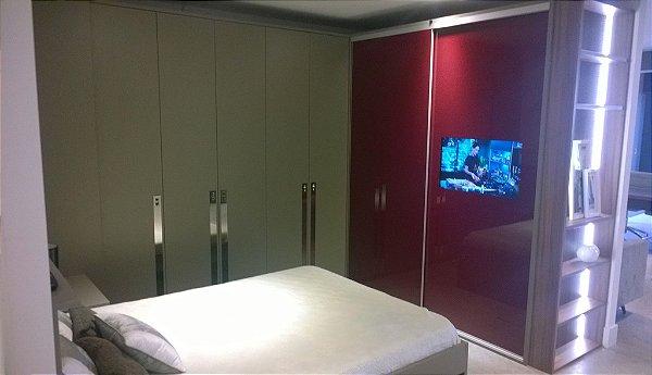Dormitório Sob Medida com portas de correr e TV embutida na porta.