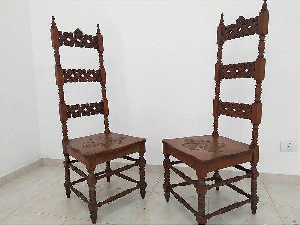 Par de cadeiras espanholas com espaldar alto entalhada no encosto , pés torneados e cartas de baralhos esculpida no acento  . Final séc XIX