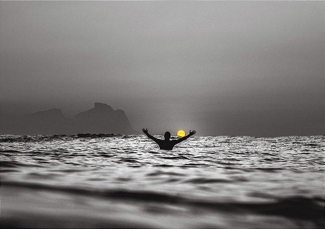 Belo nascer do sol parcialmente em preto e branco com surfista de braços abertos