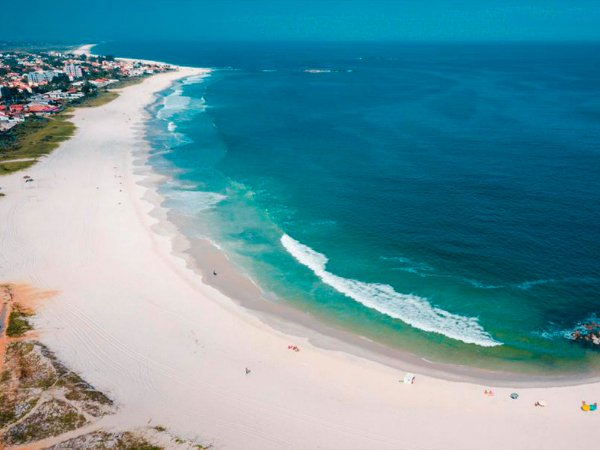 Fotografia aérea de um belo mar azul e faixa de areia